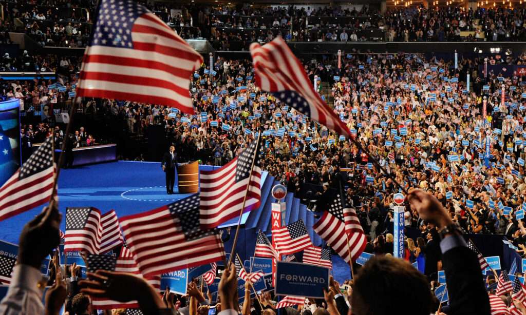 CHARLOTTE, NC - SEPTEMBER 06: (EDITORS NOTE: Re-ransmitted with alternate crop) People wave American flags as Democratic presidential candidate, U.S. President Barack Obama speaks on stage to accept the nomination for president during the final day of the Democratic National Convention at Time Warner Cable Arena on September 6, 2012 in Charlotte, North Carolina. The DNC, which concludes today, nominated U.S. President Barack Obama as the Democratic presidential candidate. (Photo by Kevork Djansezian/Getty Images) ORG XMIT: 151132414